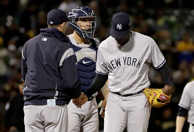 New York Yankees pitcher Luis Severino, right, hands the ball to manager Aaron Boone as he is removed during the third inning of the team