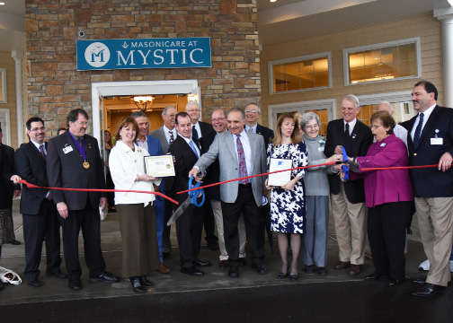 Holding the scissors at the Masonicare at Mystic, center, are Jon-Paul Venoit, president and CEO of Masonicare, and Joseph Mastronunzio, president of BROM Builders. Stonington First Selectman Rob Simmons, third from right, also helped cut the ribbon at the grand opening of the senior living residence. | Photos by Christine Corrigan, The Westerly Sun