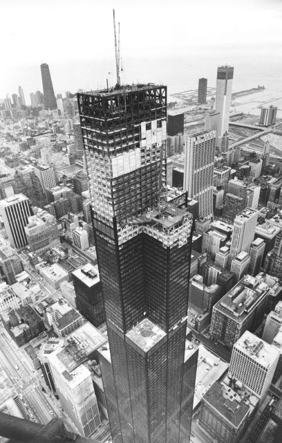 FILE - This May 3, 1973, file photo shows the topping ceremonies taking place atop the Sears Tower to mark the building reaching 1,454 feet in Chicago, from the view of from a helicopter looking northeast. Sears has filed for Chapter 11 bankruptcy protection Monday, Oct. 15, 2018, buckling under its massive debt load and staggering losses. The company once dominated the American landscape, but whether a smaller Sears can be viable remains in question. (AP Photo, File)