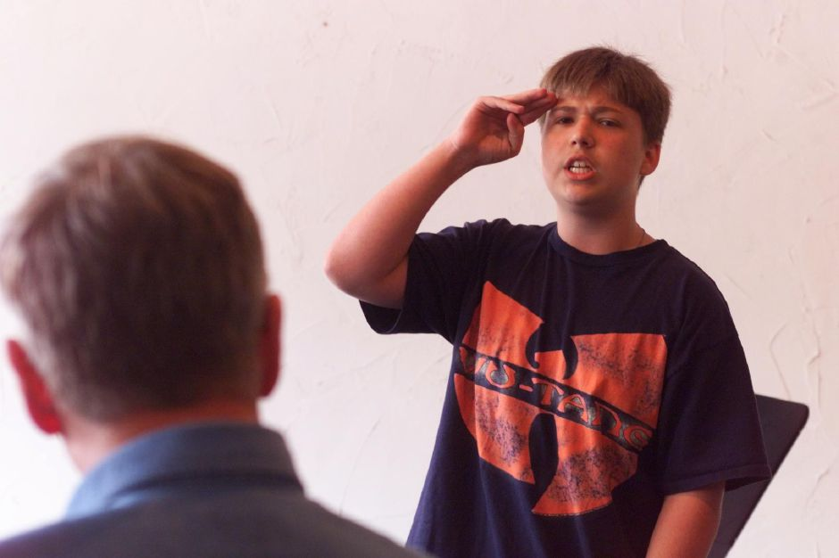 RJ file photo - Dan Houston ,13, of Wallingford emotes as he recites a poem about the Columbine High School tragedy . Dan and other area poets took part in a poerty slam at Planet Bean June 20, 1999.