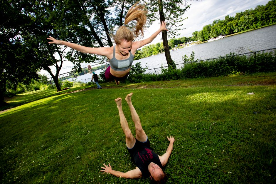 Christina Boyd gets some air as Sasha Krushnic prepares to catch her while practicing Acro Yoga along the Connecticut River in Middletown. Below, they demonstrate some other moves. Richie Rathsack, Record-Journal