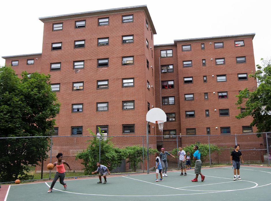 Residents of the Mills Memorial Apartments play basketball on the court off Cedar Street in Meriden, Tuesday, June 28, 2016. On Monday, The Meriden Housing Authority and the City of Meriden, along with more than two dozen participating organizations, submitted a $20 million Choice Neighborhood Implementation grant application. If awarded organizers expect it will be a catalyst for widespread and dramatic improvements downtown. | Dave Zajac, Record-Journal