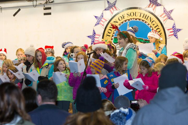 FILE PHOTO – Southington Girl Scouts sing carols on the stage at the Green Friday during White Christmas in the Community in Southington. Dec. 2, 2016 | Justin Weekes / For the Record-Journal