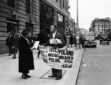 A typical scene in London, on Sept. 1, 1939, a woman buys a paper, prompted by the startling posters, to learn the latest news. (AP Photo)