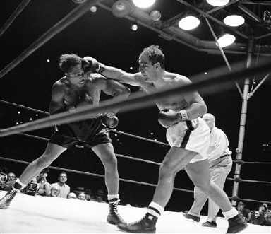 Heavyweight champion Rocky Marciano's right fist made challenger Archie Moore's hair stand on end-like this-more than once during their title bout at Yankee Stadium in New York City, Sept. 21, 1955. Marciano retained his crown when he dropped Moore by a knockout in the ninth round of their scheduled 15-round bout. Note how Moore's gloves are well away from punch in this action. (AP Photo)