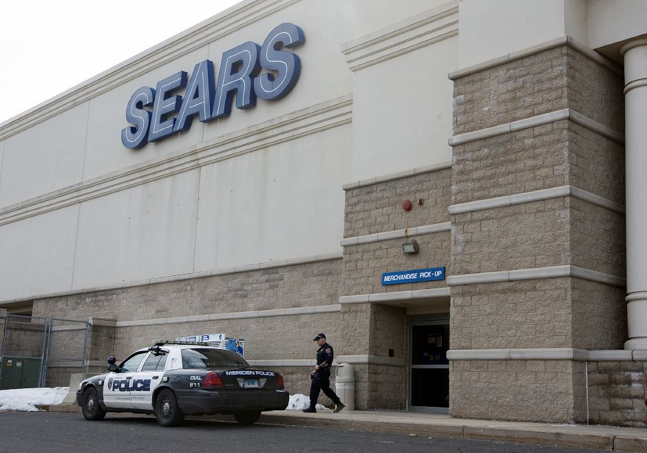 A Meriden police officer walks out of the merchandise pick-up area of Sears at the Westfield Meriden mall, Wednesday, March 11, 2015. | Dave Zajac / Record-Journal