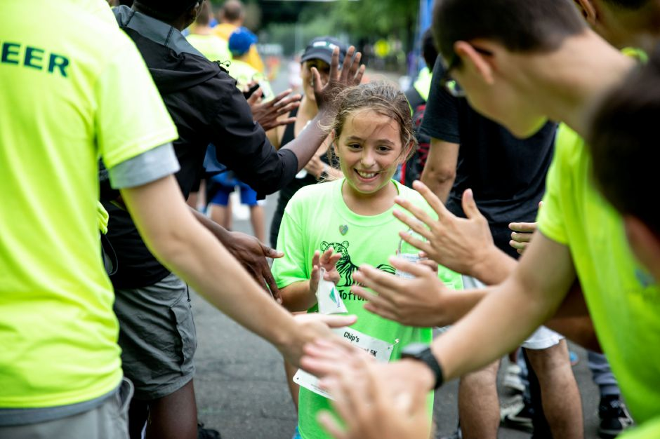 A girl is cheered on by the crowd after crossing the finish line of the Chip's Family Restaurant 5k Road Race. The Petit Family Foundation holds the race every year to raise money for the foundation