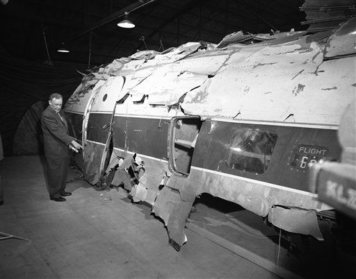 The United Airlines DC-6B which John Gilbert Graham, 23, is accused of sabotaging with a dynamite-charged time bomb, is shown after a complicated reconstruction job in Denver, Nov. 17, 1955. W.C. Mentzer, UAL executive, points to the spot where officials believe the explosion took place, killing 44 persons. At right center is 629, number of New York-to-Seattle bound flight. (AP Photo/Edward O. Eisenhand)