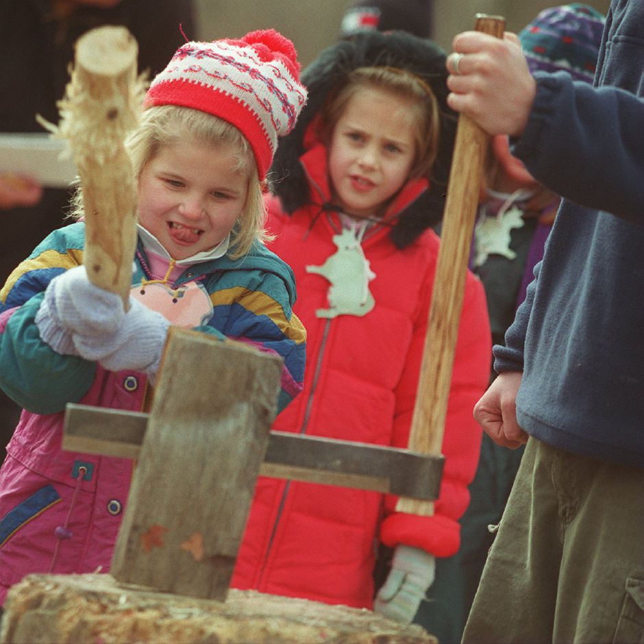"RJ file photo - Isabella Kowalski, from Highland School in Wallingford, swings a ""beetle"" to hit the ""fro"", which splits wood into thin roofing shingles, as the Dudley Farm in Guilford. Behind her is Lauren Jobmann, from Nathan Hale School in Meriden, Jan. 1999."