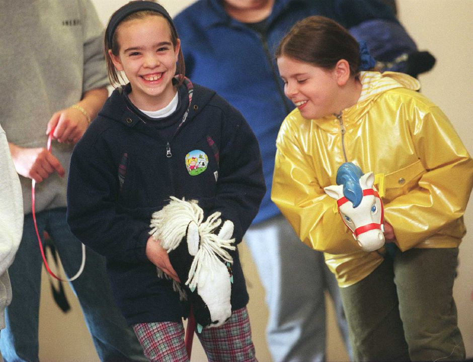 RJ file photo - Vanessa Davenport, 9, left, is in the lead in a hobby-horse race against her cousin, Jessica Regan, 8, during an AmeriCorps carnival for children, which was held at the Meriden Public Library, May 1999.