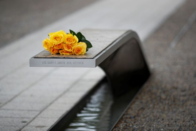 Flowers rest on a bench bearing a name in memory of retired U.S. Army Lieutenant Colonel Gary Smith before a ceremony in observance of the 18th anniversary of the September 11th attacks at the Pentagon in Washington, Wednesday, Sept. 11, 2019. (AP Photo/Patrick Semansky)