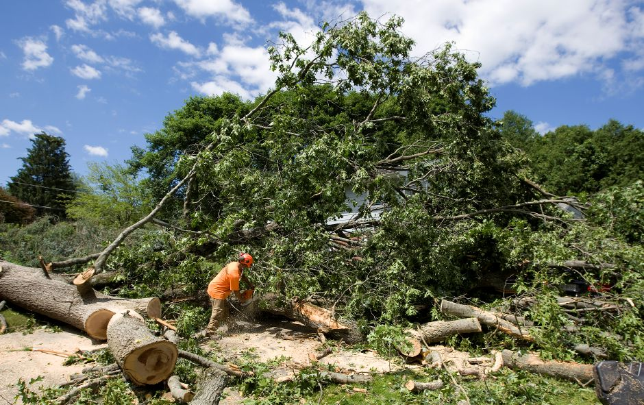 Milton Cortez, of K & J Tree Service, uses a chainsaw to cut up a large tree that fell over a vehicle and garage at 1980 Hartford Turnpike in North Haven, Wednesday, June 24, 2015. | Dave Zajac / Record-Journal