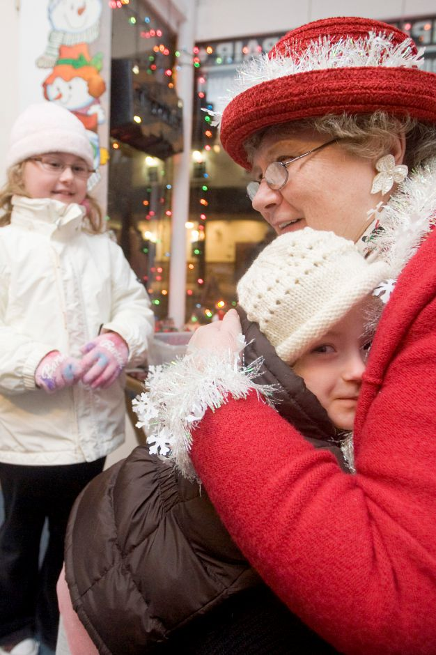 Isabelle Burek, 7, waits while her little sisiter, Kaitlyn Burek, 3, both Southington residents, hugs Ms. Clause ****MS CLAUSE REFUSED TO GIVE HER REAL NAMED**** inside CMC Computers during the Christmas in the Village of Plantsville along West Main Street, Thursday, December 2, 2010. (Johnathon Henninger/ Record-Journal)