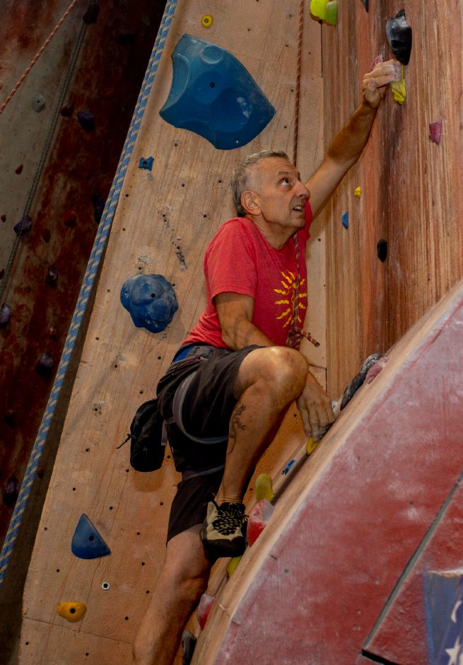 Brien Roscetti, owner, looks for his next grip on the climbing wall at Prime Climb in Wallingford Aug. 20, 2018. | Richie Rathsack, Record-Journal