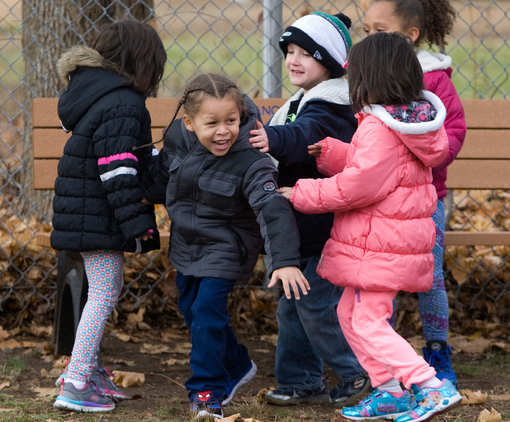 Wilfredo Narvaez, 5, second from left, smiles as fellow kindergarten students rush to visit him at the buddy bench during recess at Hanover School in South Meriden, Thursday, December 8, 2016. The Rotary Club and Meriden Public Schools recently partnered to add buddy benches to playgrounds at the city's eight elementary schools.  | Dave Zajac, Record-Journal