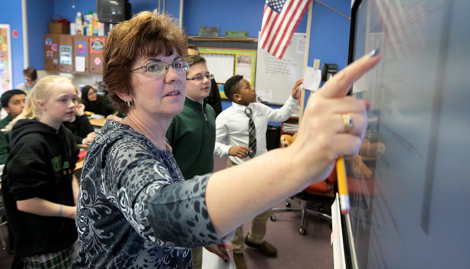Teacher Nancy Maier taps on a smart board during a language arts class at Our Lady of Mount Carmel School in Meriden, Thurs., Apr. 4, 2019. Maier has been a teacher at the school for nearly 30 years. The school is celebrating 75 years. Dave Zajac, Record-Journal