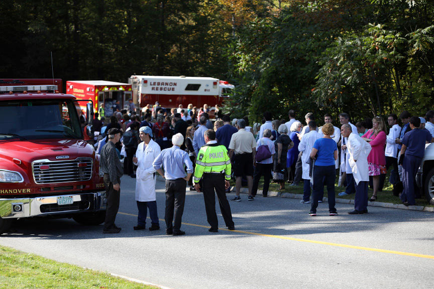 First responders, doctors, staff, patients, their family members and others wait near the main entrance of Dartmouth Hitchock Medical Center during an active shooter incident on Tuesday, Sept. 12, 2017, at the medical center in Lebanon, N.H. A family member shot and killed a 70-year-old female patient in the Intensive Care Unit earlier in the afternoon. (Charles Hatcher/The Valley News via AP)