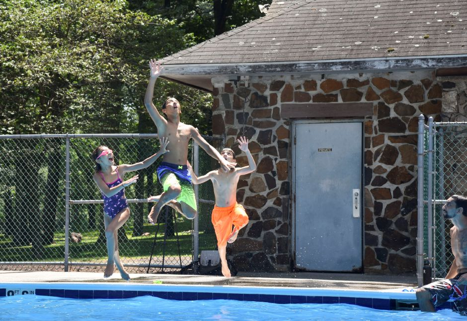 Amaliah Soto, 9, Jeremiah Soto, 12, and Noah Soto, 8, all jump for a toy their father threw at the Hubbard Park Pool in Meriden on Friday, July 19, 2019. | Bailey Wright, Record-Journal