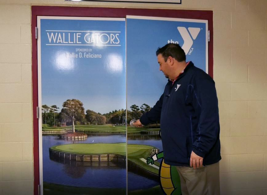 CEO John Benigni opens the door to the new golf simulator room at the Meriden YMCA, 110 W. Main St., Meriden. Friday, March 8, 2019. |Ashley Kus, Record-Journal