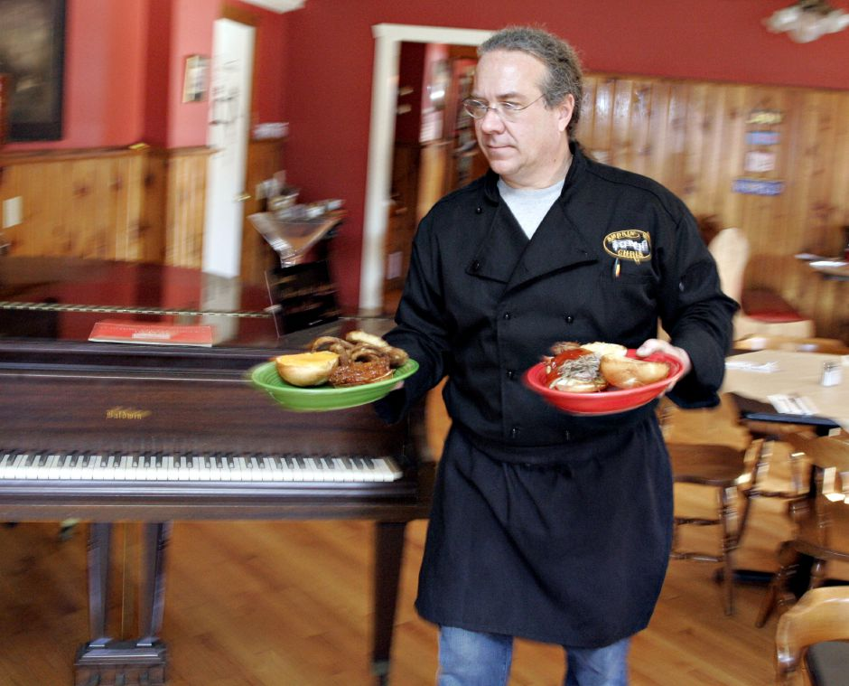 Owner and chef Chris Conlon brings out some sandwiches to serve to lunch customers at his restaurant, Smokin