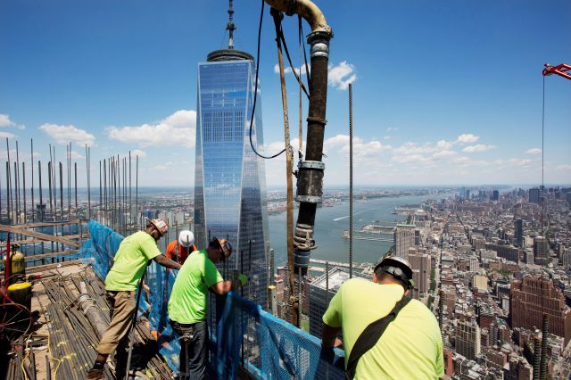 FILE - In this June 22, 2016, file photo, workers guide a boom pouring concrete on the top floor of 3 World Trade Center in New York. Behind them is One World Trade Center. The new skyscraper opens Monday. (AP Photo/Mark Lennihan, File)