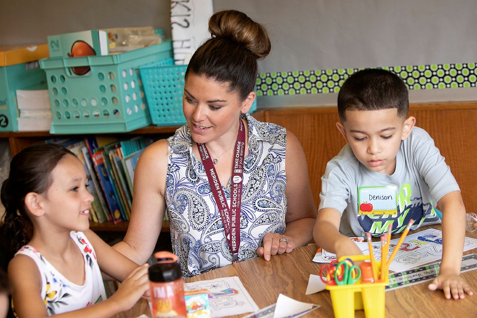 Second-grade teacher, Melissa Sciarretto, talks with students, Sarai Sepulveda, 7, and Denison Acevedo Montalvo, 7, while in her temporary classroom at Thomas Hooker Elementary School in Meriden, Monday, August 27, 2018. Sciarretto