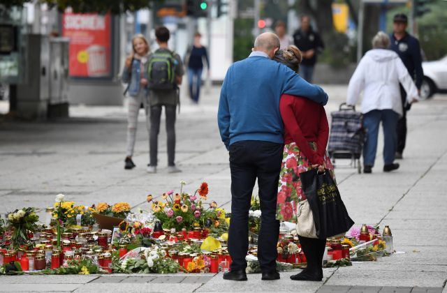 Two people stay next to candles and flowers in Chemnitz, Germany, Thursday, Aug. 30, 2018. The governor the German state of Saxony, Michael Kretschmer, traveled Thursday to the city where anger over the suspected killing of a man by migrants sparked violent protests. (Ralf Hirschberger/dpa via AP)