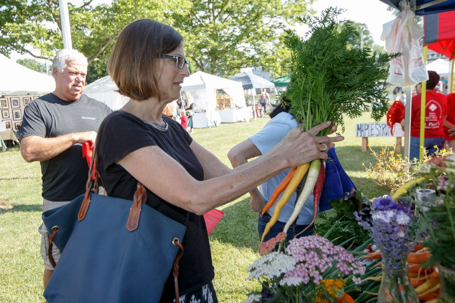 Marci Baxter of Wallingford picks out some rainbow carrots Saturday during opening weekend of the Wallingford Garden Market at Doolittle Park in Wallingford June 30, 2018 | Justin Weekes / Special to the Record-Journal