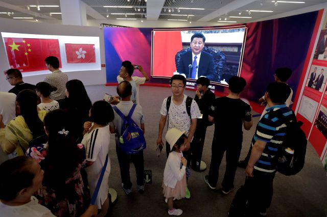FILE - In this Sunday, July 2, 2017, file photo, visitors tour at an exhibition showcasing the 20th anniversary of the return of Hong Kong to China as a screen shows Chinese President Xi Jinping delivering a speech, at National Museum in Beijing. (AP Photo/Andy Wong, File)