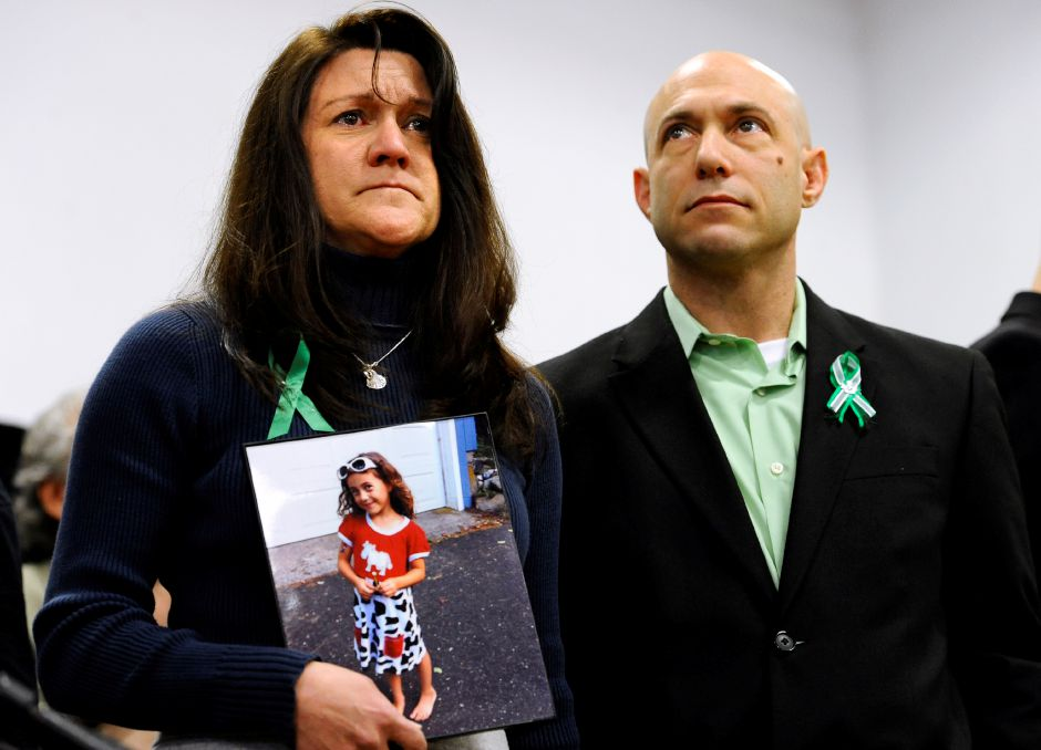 Jennifer Hensel, holding a portrait of her daughter, Sandy Hook School shooting victim Avielle Rose Richman, stands with her husband Jeremy Richman at a news conference at Edmond Town Hall in Newtown, Conn., Monday, Jan. 14, 2013. (AP Photo/Jessica Hill)