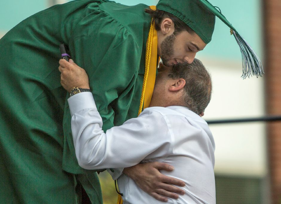 Valedictorian Jared Anziano gets a hug from his father, David Anziano, after delievering his speech during the Maloney High School graduation ceremony in Meriden Friday evening, June 19, 2015. Anziano had thanked his father for being a good role model, friend, and source of inspiration. (Christopher Zajac / For the Record-Journal)