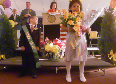 The 2002 Little Miss Daffodil, (r) Justice Empronto Gale, 7, a 2nd grader at Mr. Carmel and her honor escort, (L) Caleb Santana, 6, a 1st grader at Nathan Hale, are introduced to the crowd after being crowned Wednesday evening in the 24th annual ceremony at Hubbard Park.  In the background from left to right are, this yaers parade marshal, Jack Harrison, (C) Mayor Mark Benigni and Doreen Roddy a member of the Daffodil Festival Committee.  Gale and Santana will ride in Saturday