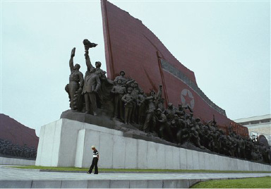 A lone stroller passes a collection of statues outside a museum in Pyongyang, the North Korean capital, Aug. 22, 1990. The memorial is dedicated to the 1950-53 Korean War, when North Korea battled the United States and troops from other nations. (AP Photo/Vincent Yu)