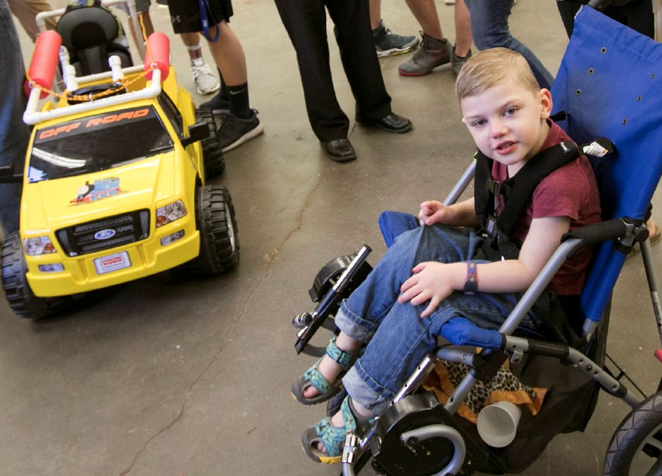 Henry Curylo, 4, of Southington, waits for his electric car to be finished by students at Southington High School Friday, May 11, 2018. Students from Southington High School and Central Connecticut State University made the final fittings to battery-powered cars for two special needs children. Dave Zajac, Record-Journal