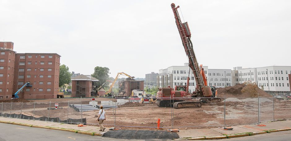 Demolition crews, background, take down a building in the former Mills Memorial Apartments complex next to the new Meriden Commons, right, in downtown Meriden, Friday, August 17, 2018. Construction on Meriden Commons II, foreground, continues along Park Street and Cedar Street. Dave Zajac, Record-Journal