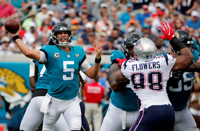 Jacksonville Jaguars quarterback Blake Bortles (5) throws a pass as he is pressured by New England Patriots defensive end Trey Flowers (98) during the first half of an NFL football game, Sunday, Sept. 16, 2018, in Jacksonville, Fla. (AP Photo/Stephen B. Morton)