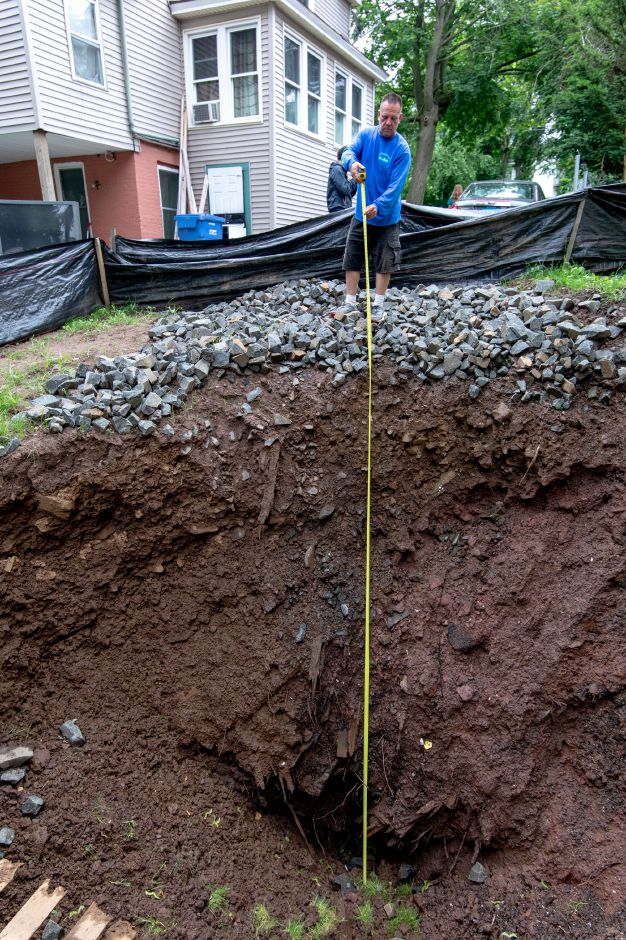 A property manager with Dockside Construction shows the size of a sinkhole which appeared in the backyard of 170 Liberty Street in Meriden on Easter morning. | Devin Leith-Yessian/Record-Journal