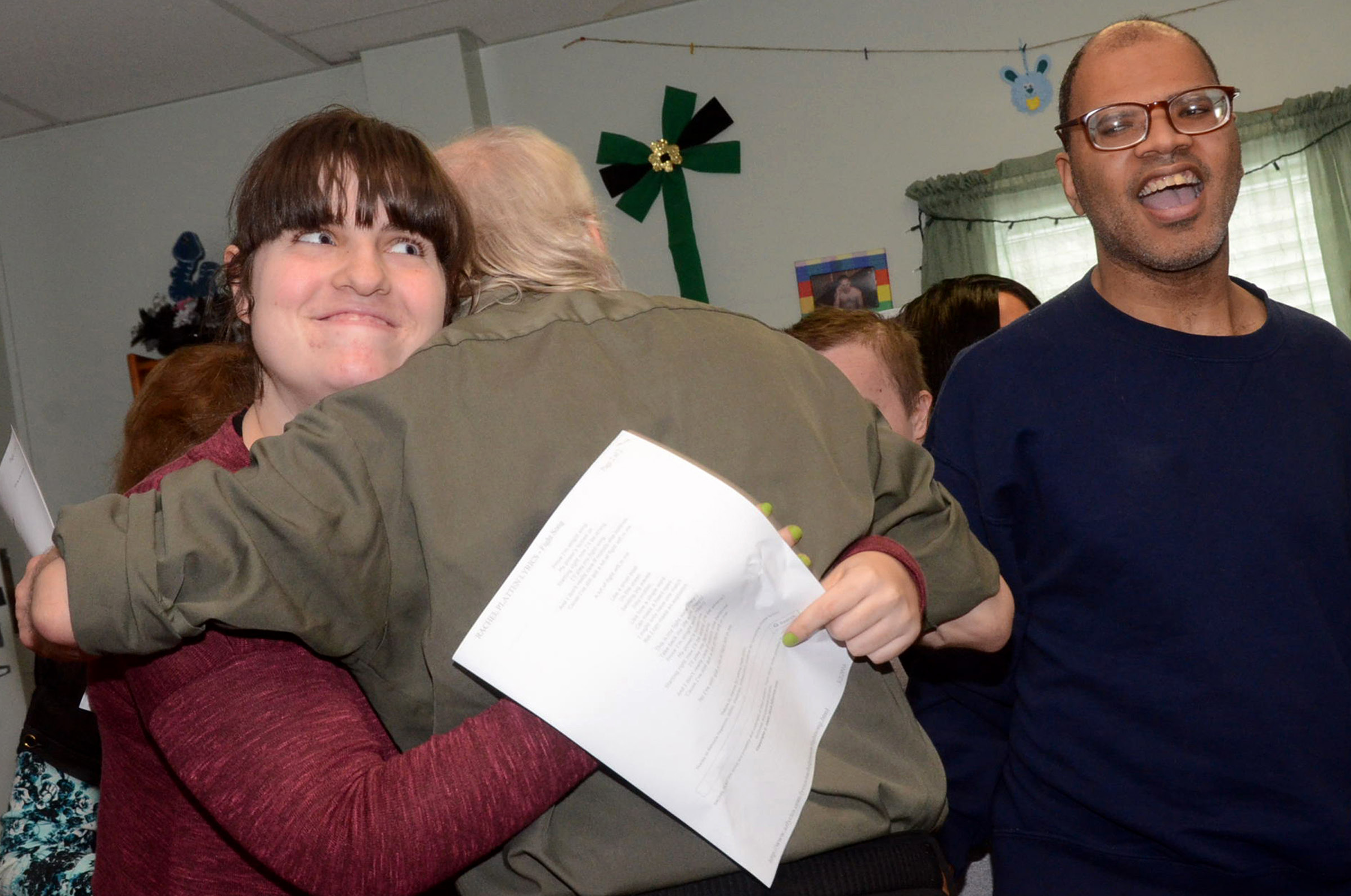 Christopher Kerrick, of ReDCO, gives consumer Kayla Senick a hug after she and Octbarr Jarmon, right, both members of the chorus performed, as consumers, staff and family members at ReDCo Group along with Luzerne-Wyoming Counties Mental Health and Developmental Services celebrate Intellectual Disability Awareness Month during a program held Wednesday, March 16, 2016, at ReDCo in Hazleton, Pa.  (Ellen F. O