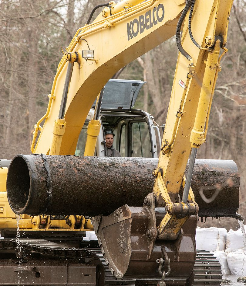 A worker maneuvers an excavator to remove a section of 30-inch pipe from the Quinnipiac River during the final phase of the Quinnipiac River barrier removal project in Meriden, Fri., Apr. 5, 2019. Dave Zajac, Record-Journal