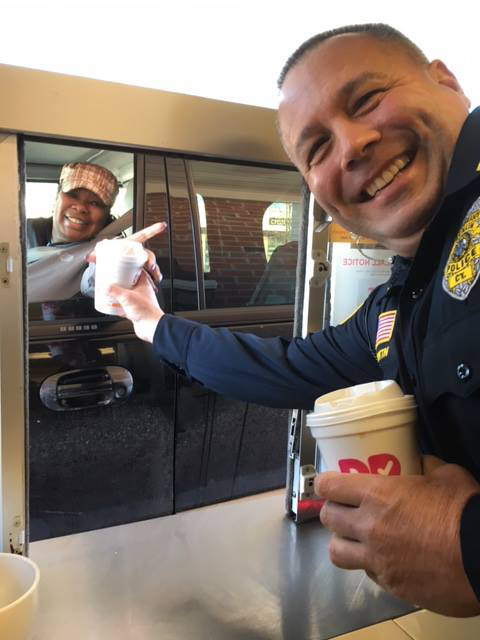 "Berlin Police Sgt. Todd Lentini hands coffee to a customer during ""coffee from a cop"" on Thursday, March 16. 