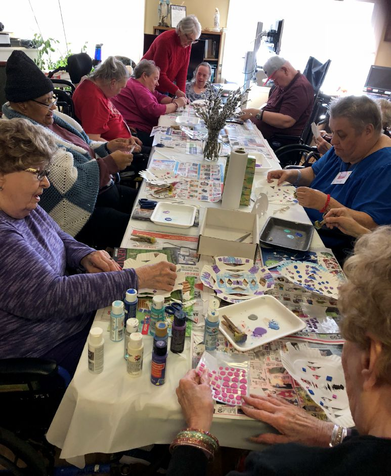 Skyview residents cutting and decortaing paper plate snowflakes.