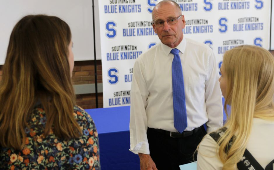 Newly appointed Southington girls basketball coach Howie Hewett talks with players Alison Barretta, left, and Karoline Barrett prior to his introductory press conference on Thursday at Southington High School. | Spencer Davis, Record Journal