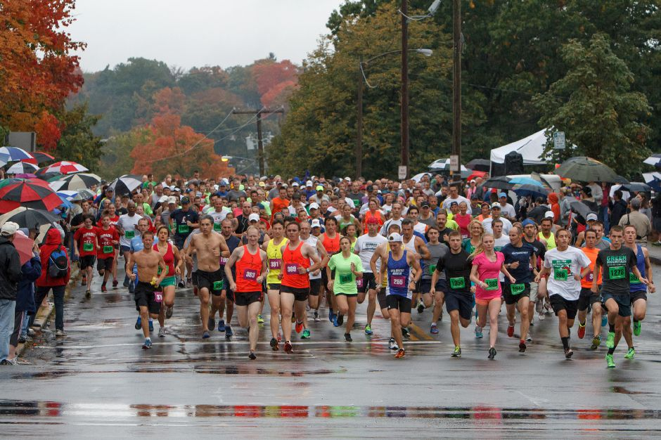 Runners start the Apple Harvest Road Race in the rain on Columbus Ave. in Southington Sunday October,6 2013 | (Justin Weekes / For the Record-Journal)