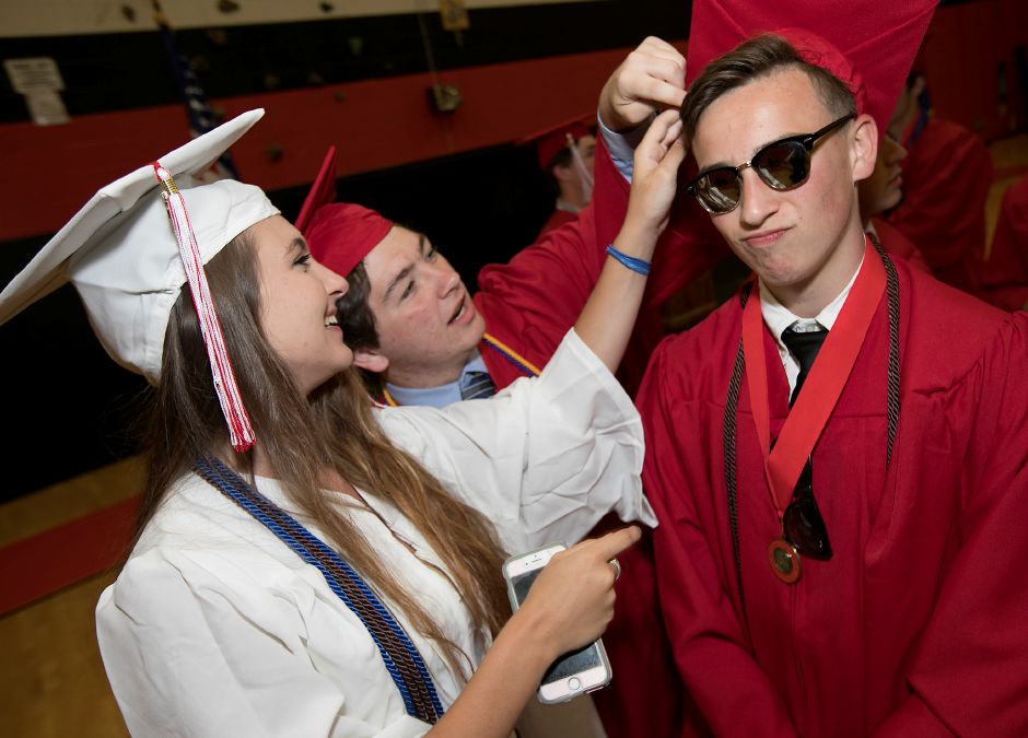 Graduate Evan Russo gets assistance with his cap during graduation ceremonies at Cheshire High School, Wednesday, June 14, 2017. | Dave Zajac, Record-Journal