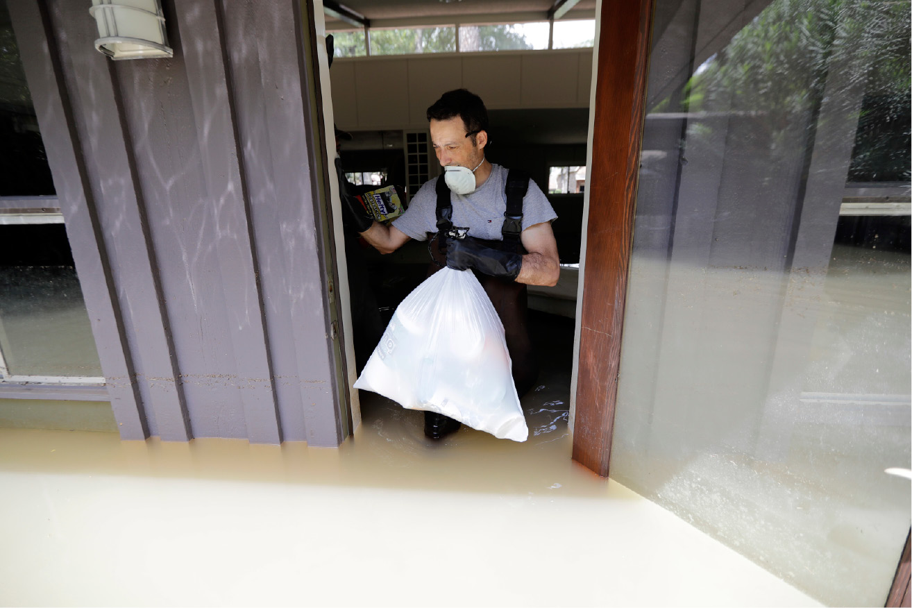 Gaston Kirby walks through floodwaters as he leaves his home in the aftermath of Hurricane Harvey, Monday, Sept. 4, 2017, near the Addicks and Barker Reservoirs, in Houston. (AP Photo/David J. Phillip)