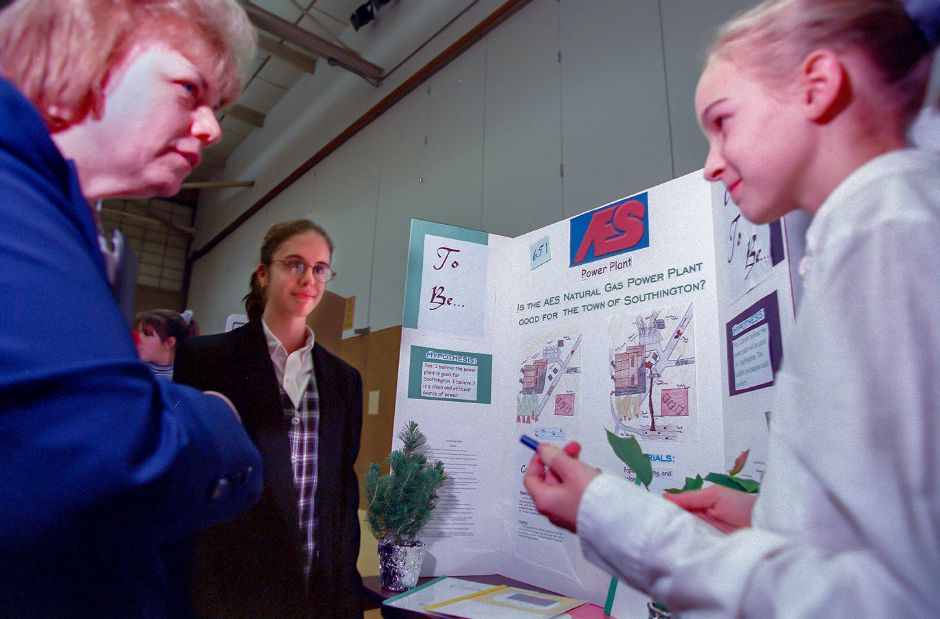 RJ file photo - Students Nina DePalma, center, and Marisa Soboleski, right, discuss their project about the AES power plant with science fair judge Dale Riedinger in Southington, Jan. 1999.