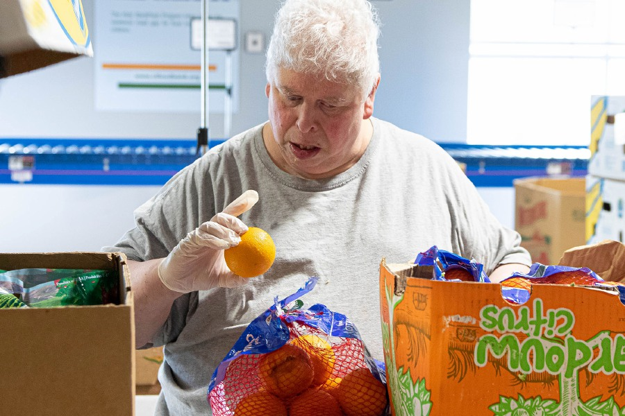 Volunteer Anthony Daniel of East Haven inspecets oranges before it is put into the warehouse at the Connecticut Food Bnk in Wallingford on Thursday September 5, 2019. Aaron Flaum, Record-Journal