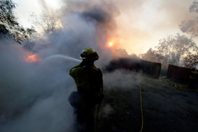 A Los Angeles County firefighter puts water on a burning car during a wildfire in the Lake View Terrace area of Los Angeles Tuesday, Dec. 5, 2017.  Ferocious winds in Southern California have whipped up explosive wildfires, burning a psychiatric hospital and scores of other structures. Tens of thousands of people have been ordered evacuated. (AP Photo/Chris Carlson)