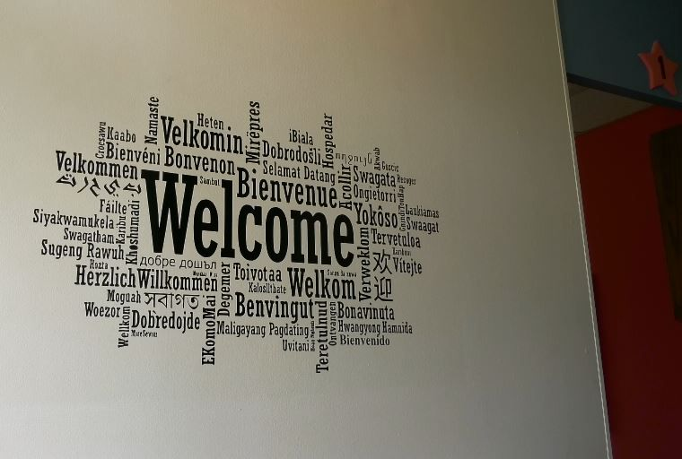 The welcome sign displayed in different languages in the front lobby of Small World Languages in Cheshire, 205 Academy Road. |Ashley Kus, Record-Journal