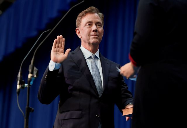 Connecticut Gov. Ned Lamont takes the oath of office administered by former Chief Justice Chase T. Rogers, Wednesday, Jan. 9, 2019, inside the William A. O